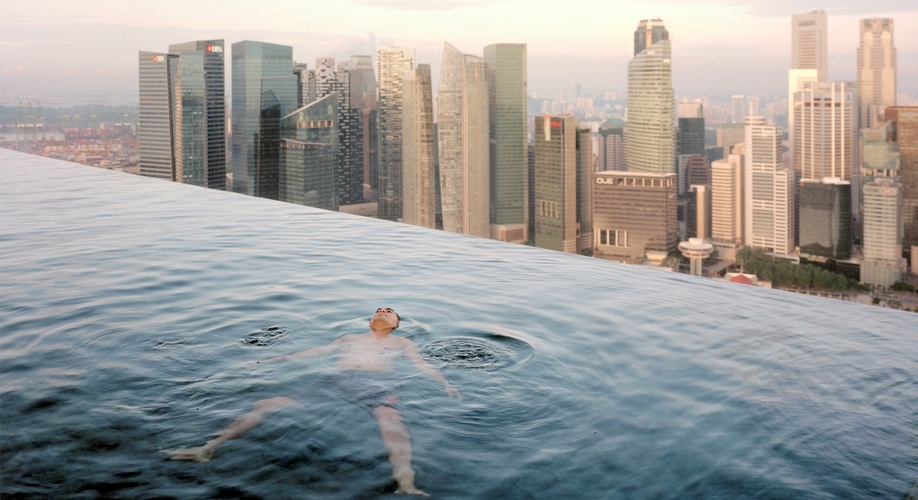 Paolo Woods and Gabriele Galimberti, (INSTITUTE),  Man in swimming pool from, The Heavens, (Singapore 2013)